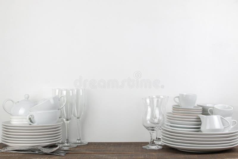 Una pila de platos vajilla en una tabla de madera marrón platos para servir la tabla placas y cubiertos, tazas y tetera, vidrios imagen de archivo
