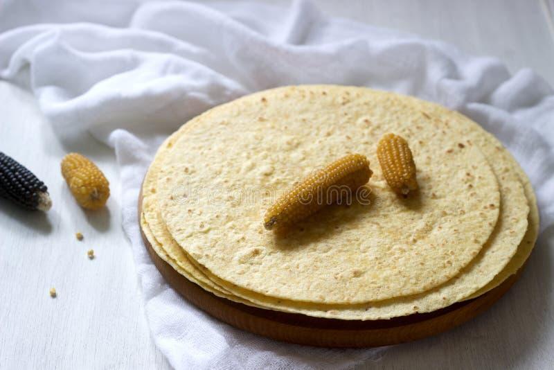 Una pila de tortillas de maíz redondas en un tablero de madera y mazorcas de maíz fotografía de archivo libre de regalías