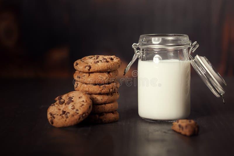 Una pila di biscotti di pepita di cioccolato con latte sulla vecchia tavola di legno scura fotografia stock