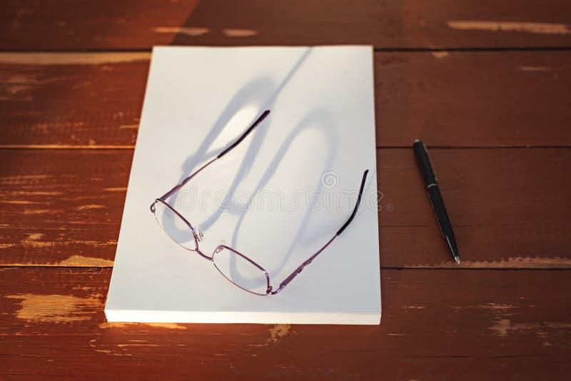Una pila di fogli bianchi di carta, di una penna e dei vetri su una tavola di legno rossa immagine stock