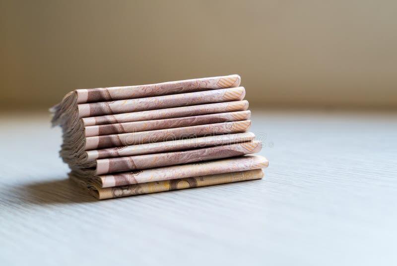 Una pila di mille soldi tailandesi del bagno sulla tavola di legno fotografia stock libera da diritti