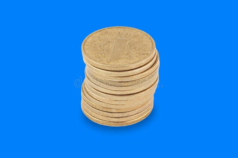 Una pila di molte monete gialle nel centro su fondo blu fotografia stock