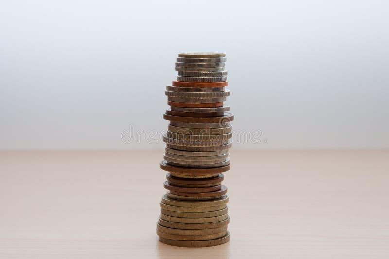 Una pila di monete dei paesi differenti, della dignità differente, del colore e della dimensione sulla tavola nel centro dell'imm fotografia stock libera da diritti