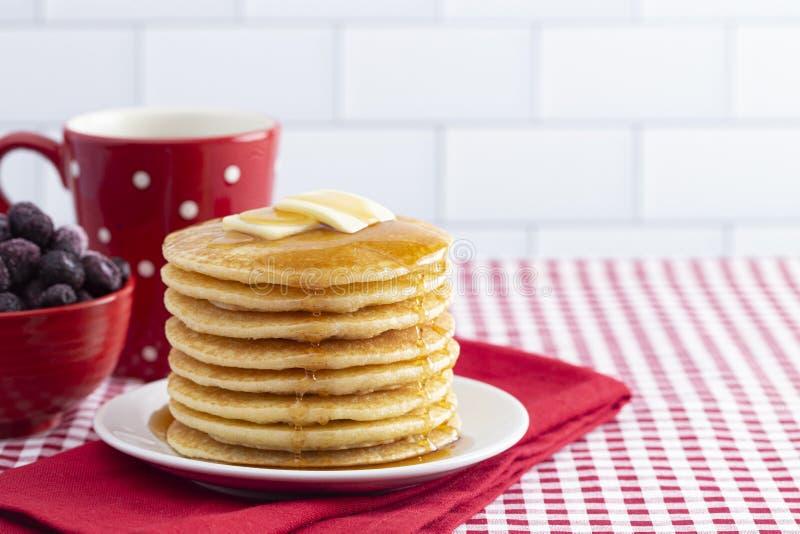 Una pila di pancake appena fatti su una tovaglia del percalle immagini stock