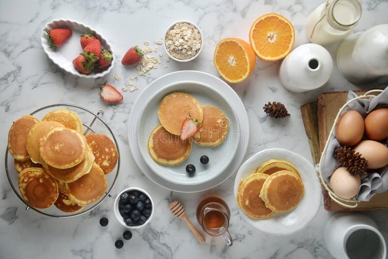 Una pila di pancake con i mirtilli, fragole, arancio sulla tavola di marmo bianca fotografia stock libera da diritti
