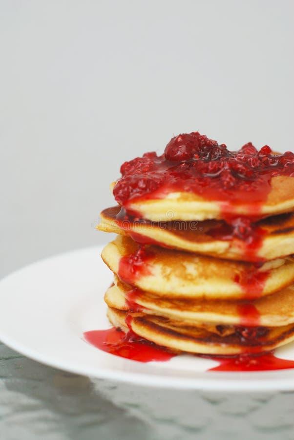 Una pila di pancake con l'inceppamento di fragola isolato sul piatto bianco e sul fondo grigio fotografie stock
