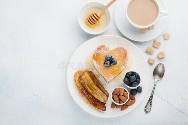Una pila di pancake deliziosi con miele, caffè ed i mirtilli su un fondo blu-chiaro Grande prima colazione per fotografia stock libera da diritti