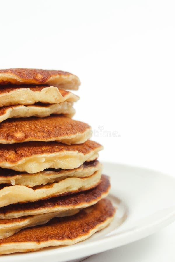 Una pila di pancake puri su un fondo bianco del piatto Isolato fotografia stock libera da diritti