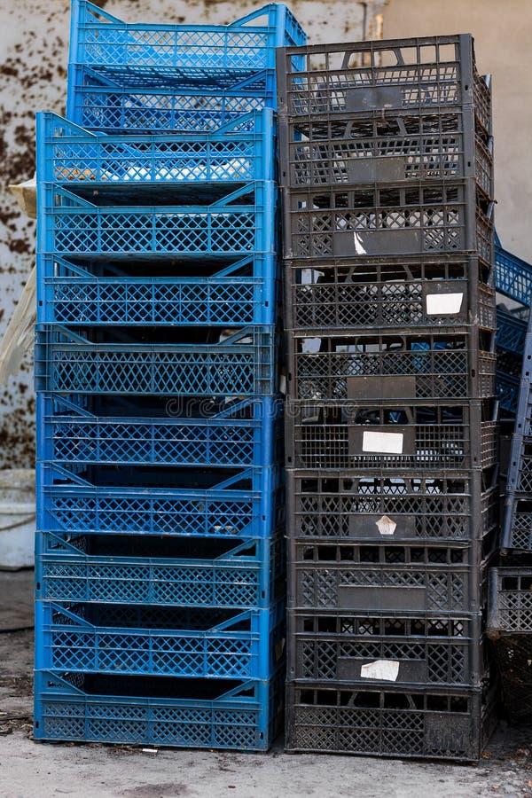 Una pila di scatole di plastica vuote blu e nere per la conservazione ed il trasporto le verdure e della frutta fotografie stock libere da diritti
