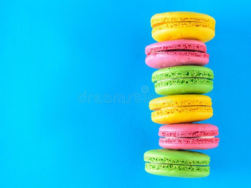 Una pila di sei dolci variopinti del maccherone su un fondo blu immagine stock libera da diritti