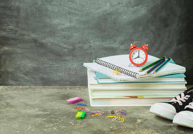 Una pila di taccuini educativi della sveglia dei libri sui precedenti di un bordo di gesso Il concetto di nuovo alla scuola immagine stock libera da diritti