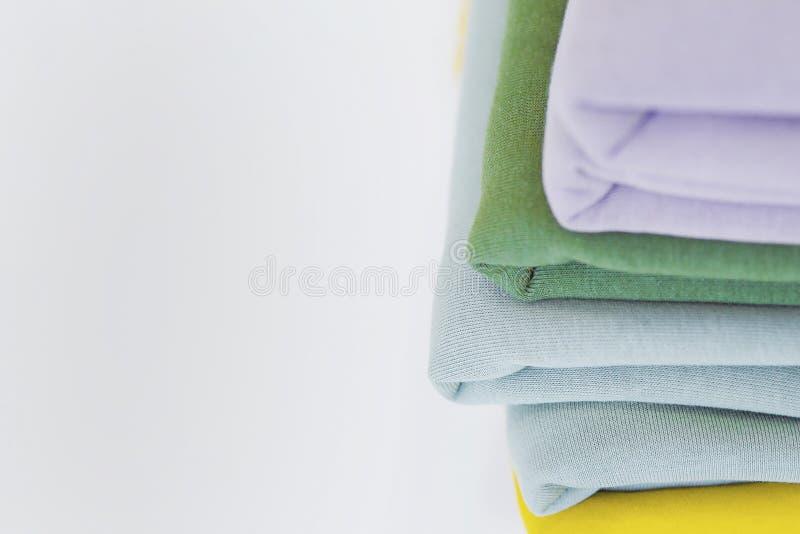 Una pila di tessuti per il cucito sulla tavola di tessuti colorati Multi per adattare Un mucchio dei tessuti per i vestiti di cuc fotografia stock