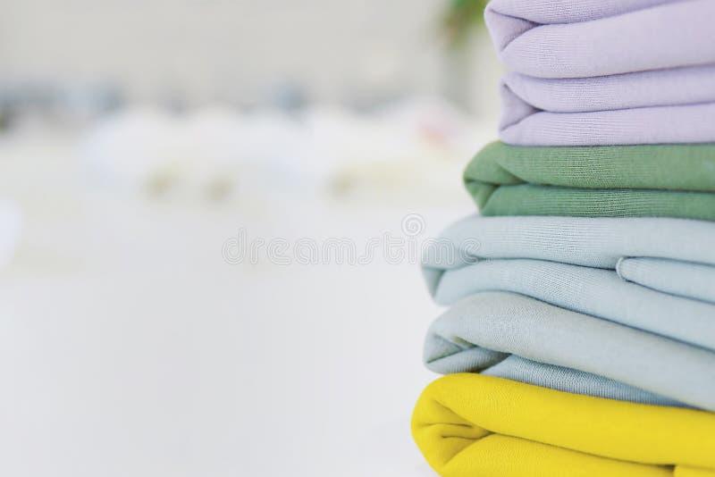 Una pila di tessuti per il cucito sulla tavola di tessuti colorati Multi per adattare Un mucchio dei tessuti per i vestiti di cuc immagine stock