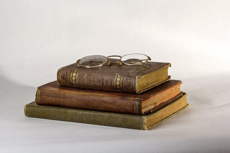 Una pila di tre libri antichi con un paio degli occhiali d'annata fotografia stock libera da diritti