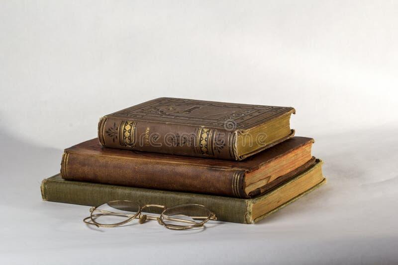 Una pila di tre libri antichi con un paio degli occhiali d'annata immagine stock libera da diritti