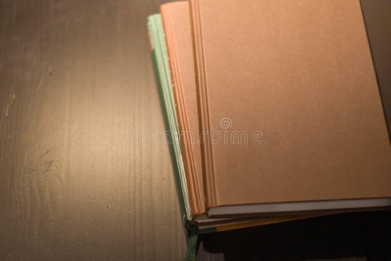 Una pila di tre libri si trova su una tavola di legno fotografie stock libere da diritti