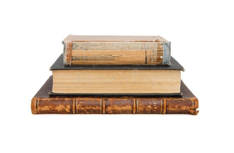 Una pila di tre vecchi libri isolati fotografie stock