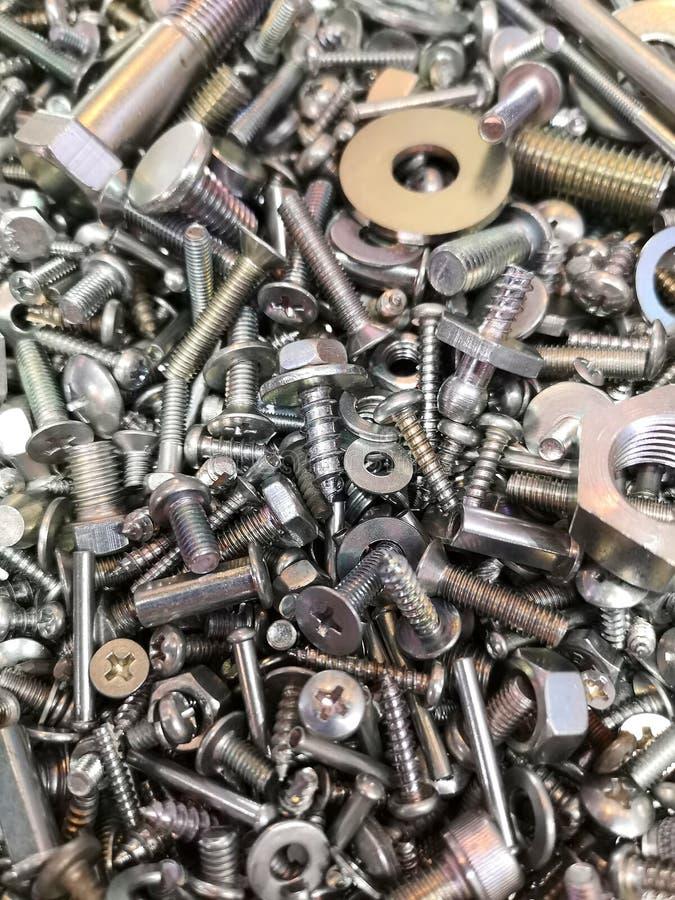 Una pila grande e interesante de nueces nuevas y brillantes del metal - y - pernos, tornillos y lavadoras imagenes de archivo