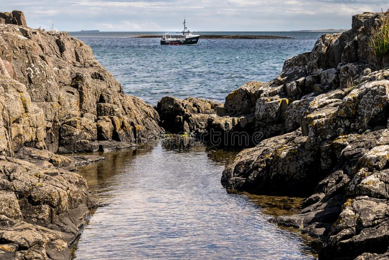 Una piscina de la roca con agua y una nave en el mar imagen de archivo
