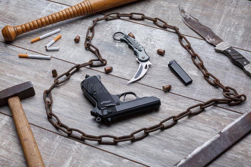Una pistola, coltello, catena del metallo, battito, un martello e parecchie sigarette con un accendino fotografia stock libera da diritti