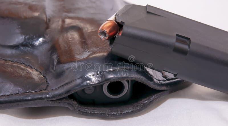 Una pistola negra de 9m m en una pistolera de cuero con una revista cargada con las balas huecos del punto encima de ella imagen de archivo libre de regalías