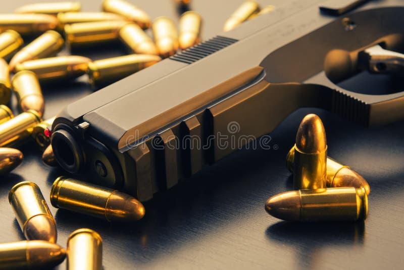 una pistola semiautomatica da 9 millimetri con le pallottole sparse intorno su superficie nera immagini stock libere da diritti