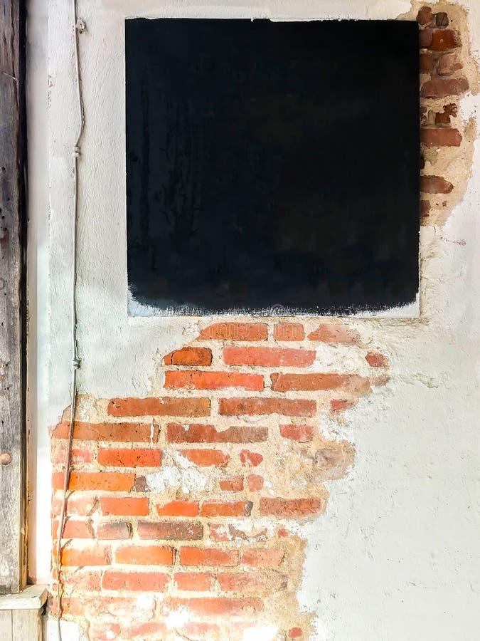 Una pizarra y pared de ladrillo en blanco imagenes de archivo