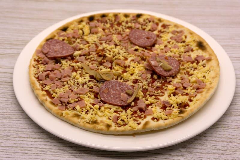 Una pizza de salchichones congelada en una tabla de cortar de madera fotografía de archivo libre de regalías