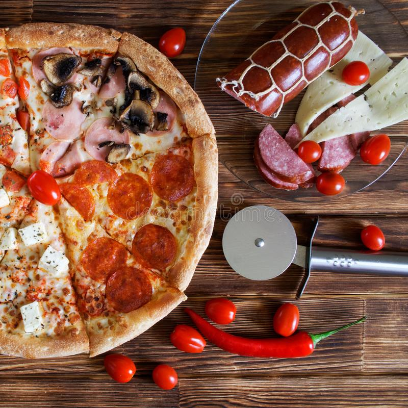 Una pizza del quattro-pezzo con le bugie delle merguez, del prosciutto, dei funghi, del salame, del formaggio e dei pomodori sui  immagini stock