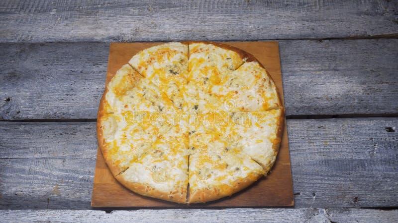 Una pizza deliziosa calda di quattro formaggi che si trova su un vassoio sul fondo grigio di legno dei bordi Pagina Chiuda su per immagine stock libera da diritti