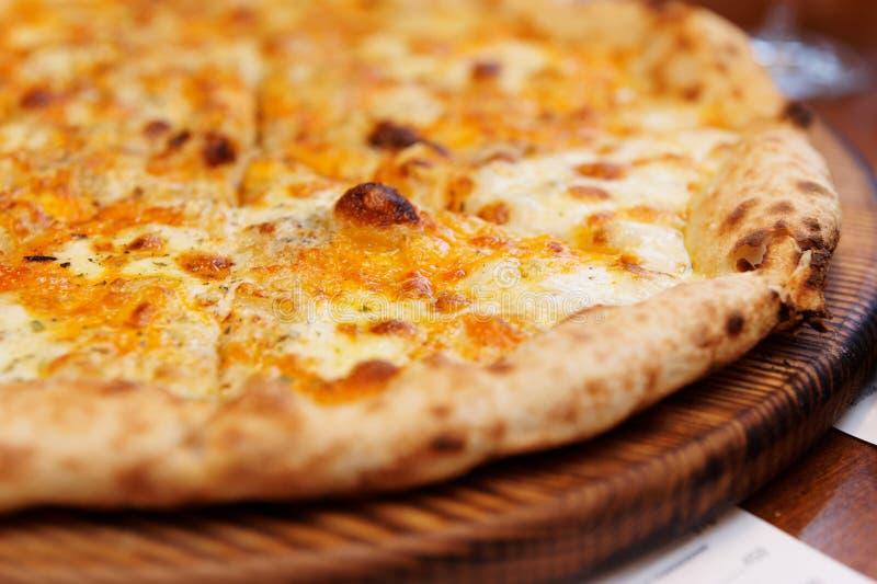 Una pizza di quattro formaggi sul bordo servente fotografia stock libera da diritti