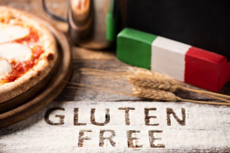 Una pizza libre del gluten en un fondo de madera rústico fotografía de archivo