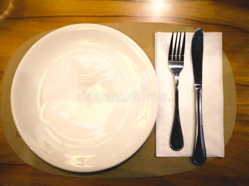 Una placa blanca con la bifurcación de plata y cuchillo para comer la pizza eso imagenes de archivo