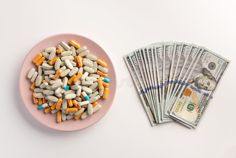Una placa con las píldoras y los billetes de banco del dólar americano aislados en blanco foto de archivo libre de regalías