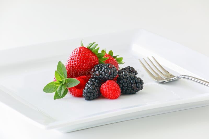 Una placa de bayas maduras frescas en un fondo blanco incluyendo las fresas, las zarzamoras, y las frambuesas foto de archivo libre de regalías