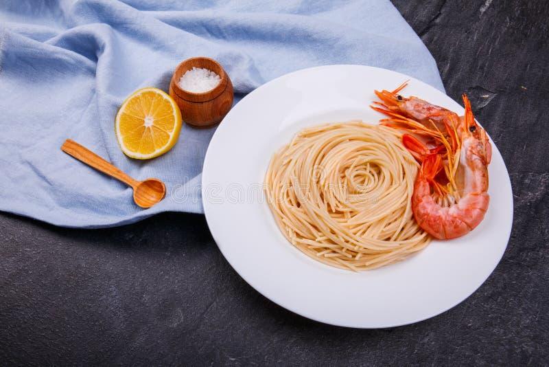 Una placa de espaguetis con los camarones, una rebanada de limón y un sal-pote fotografía de archivo