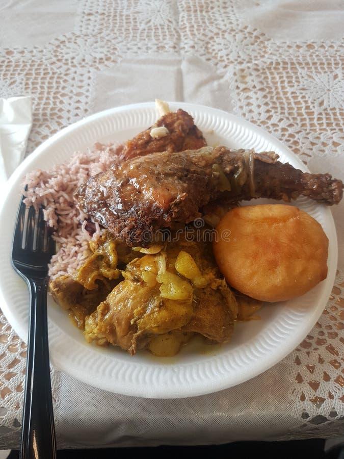 Una placa de la bola de masa hervida frita cocina sabrosa carribean típica, arroz y guisantes y pollo picante del tirón fotos de archivo