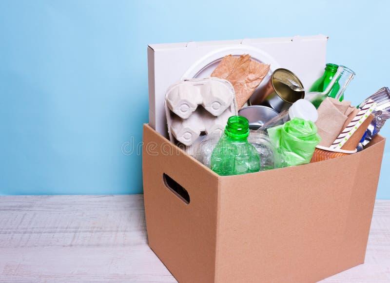In una plastica della scatola di cartone, bottiglie di vetro, latte, carta Il concentrato immagine stock
