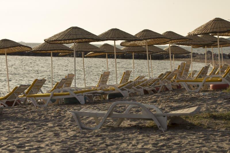Una playa arenosa vacía con las camas del colchón amarillo y los paraguas de la paja que broncean fotos de archivo libres de regalías