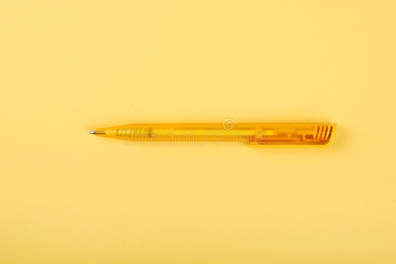 Una pluma amarilla en una hoja de papel amarilla fotografía de archivo