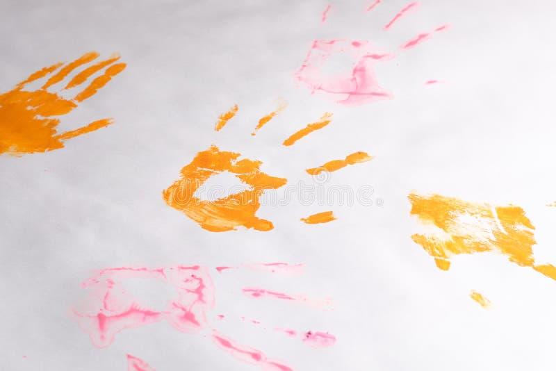 Una poca impresión de las manos en un fondo del Libro Blanco, manos multicoloras del ` s de los niños fotografía de archivo