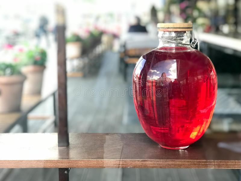 Una poder de cristal grande del tres-litro de campote, jugo, pociones con brillar intensamente líquido con una tapa de madera en  fotografía de archivo libre de regalías