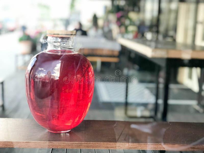 Una poder de cristal grande del tres-litro de campote, jugo, pociones con brillar intensamente líquido con una tapa de madera en  foto de archivo libre de regalías