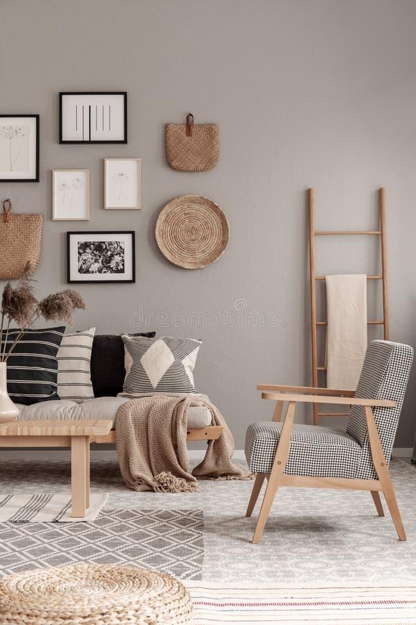 Una poltrona elegante e vintage all'interno del salotto contemporaneo, una scala futon e una scandinava di legno con una coperta immagine stock libera da diritti