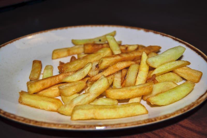 Una porción de patatas fritas en un primer blanco del plato foto de archivo libre de regalías