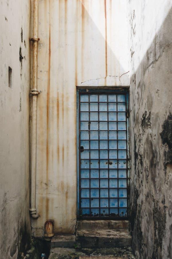 Una porta blu nel fratempo delle pareti immagini stock