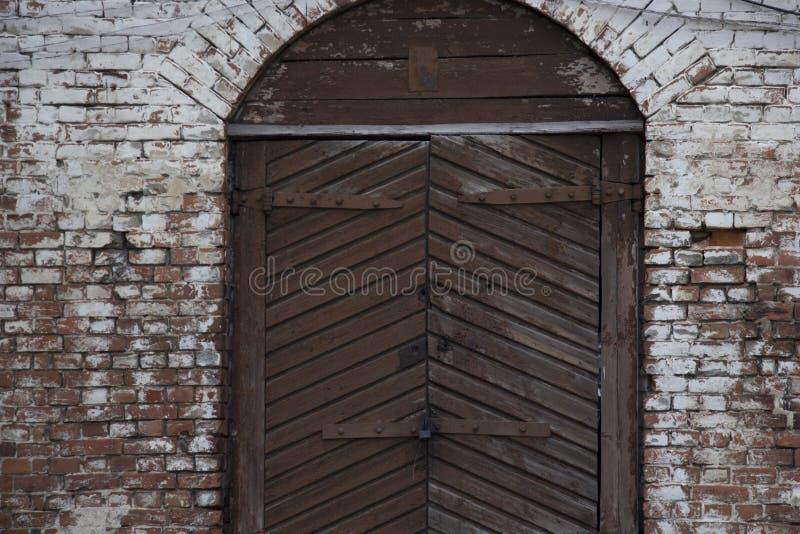Una porta di legno del garage in una parete di pietra annata fotografia stock