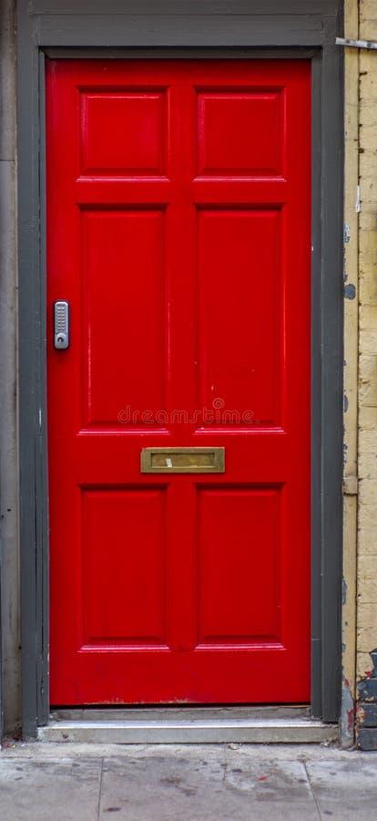 Una porta rossa nelle vie di Londra di estate fotografia stock libera da diritti