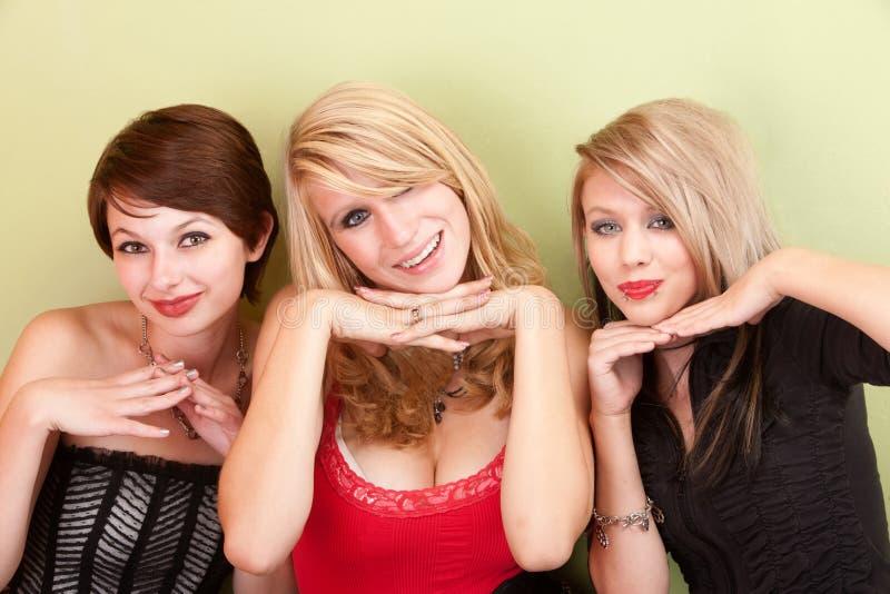 Una posa teenager attraente delle tre ragazze con le loro mani fotografia stock