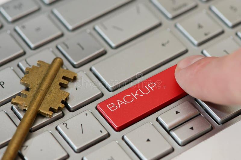 Una prensa del finger un botón con la copia de seguridad del texto en un teclado fotografía de archivo